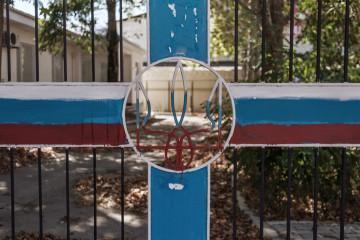 Украинский герб перекрашеный в цвета российского флага на воротах одной из военных частей ВМСУ.