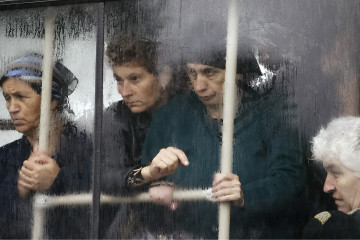 BESLAN, RUSSIA - SEPTEMBER 06:  The women look out of the bus window in the rain on a mass funeral of those killed in the school hostage crisis on September 6, 2004 in Beslan, southern Russia. More than 350 people died after Chechen militant hostage-takers and Russian forces began a firefight that ended violently for more than 1200 held captive inside the school for three days. Oleg Nikishin/Epsilon Photo)
