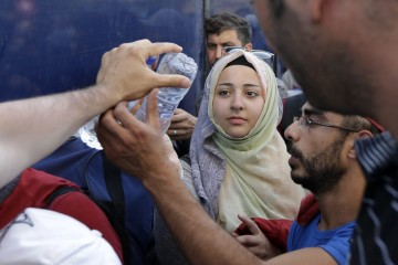 Syrian migrants, who have been stranded for days, in the northeastern Greek island of Lesvos, receive water as they wait for travel documents from Greek authorities at the port of Mytilene on Monday, June 15, 2015. An emergency European Union plan to help Italy and Greece manage thousands of migrants crossing the Mediterranean could be vastly watered down on Tuesday, according EU diplomats. During the first five months of 2015, 40,297 migrants arrived in Greece, up from 6,500 in the same period in 2014. Almost all of them have crossed in boats from Turkey.