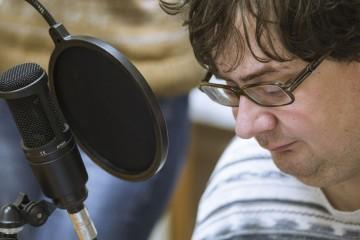 """Михаил Ларсов, ведущий и автор передач на радиостанции """"Зазеркалье"""" во время прямого эфира."""