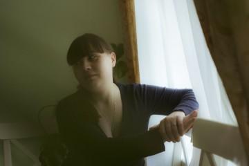 Лиля сидит у окна и смотрит всторону где спит дочь