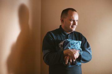 Саша в коридоре тренировочной квартиры. Собирается отнести бельё, которое только что погладил сам.