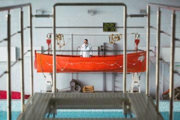 Сергей Михайлович в спасательной шлюпке в тренировочном бассейне Морского колледжа. Новая работа Сергею Михайловичу нравится, но в ней много рутины. Он скучает по морю. Говорит, что если бы мог, тут же снова отправился в плавание. Хотел бы пройти по новому каналу между Тихим и Атлантическим океаном, который ещё только строится. Но обязательно рабочим на судне, потому что плыть пассажиром – это скучно.