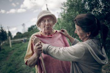 Елена, основатель фермы в деревне Упрямово, прикладывает кофточку к Нине Васильевне.