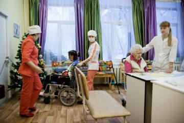 Сотрудники хосписа помогают украшать пациентам елку их поделками.