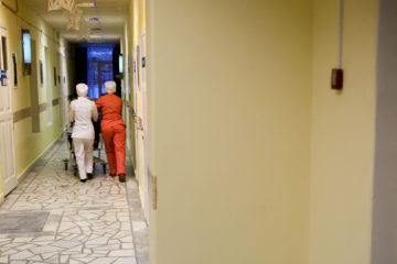 Практикантки сопровождают пациентку до палаты.