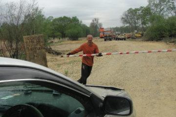 Один из работников компании ООО Ферум открывает шлагбаум, чтобы пропустить автомобиль с хлебом  Фото: Виктория Микиша