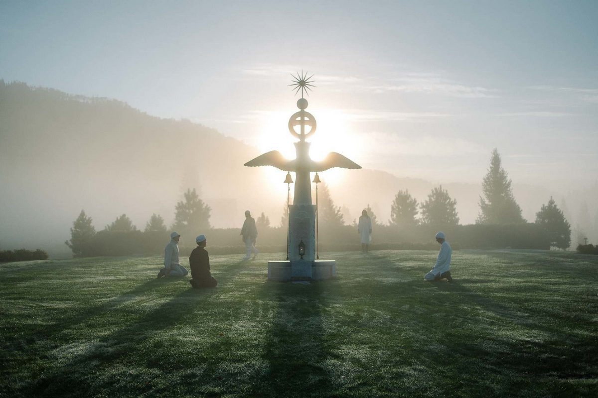 На фотографии странная фигура с крестом и крыльями стоящая посреди поляны. Вокруг фигуры, обратившись к ней, на коленях сидят люди. Фото снято на закате, позади фигуры садится солнце.