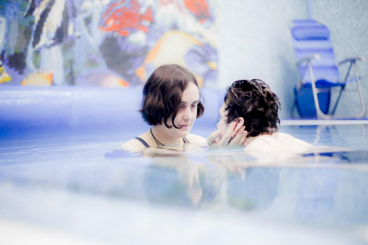 На фотографии молодая женщина, стоя по шею в бассейне, держит в ладонях лицо мальчика.