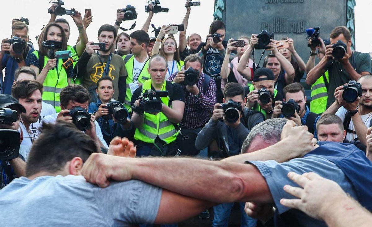 На фотографии на переднем плане мужчины деруться между собой. На заднем плане толпа людей в жёлтых жилетах с фото- и видеокамерами. В одном из людей на заднем плане можно узнать корреспондента телеканала Дождь Лёшу Коростелёва